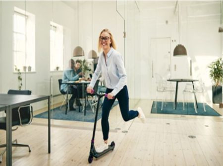 Happy employee businesswoman riding scooter at work office space planning